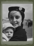 Taylor carries her baby son Michael Howard, only 7 months, at London Airport in 1955.